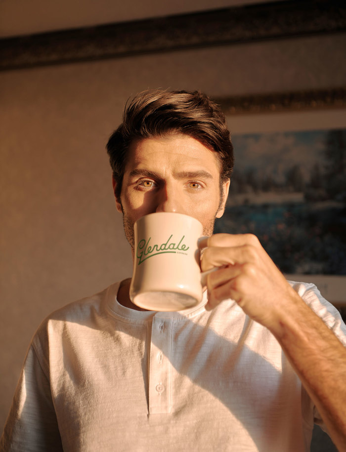 Man drinking coffee out of a white mug with the Glendale Express logo on it