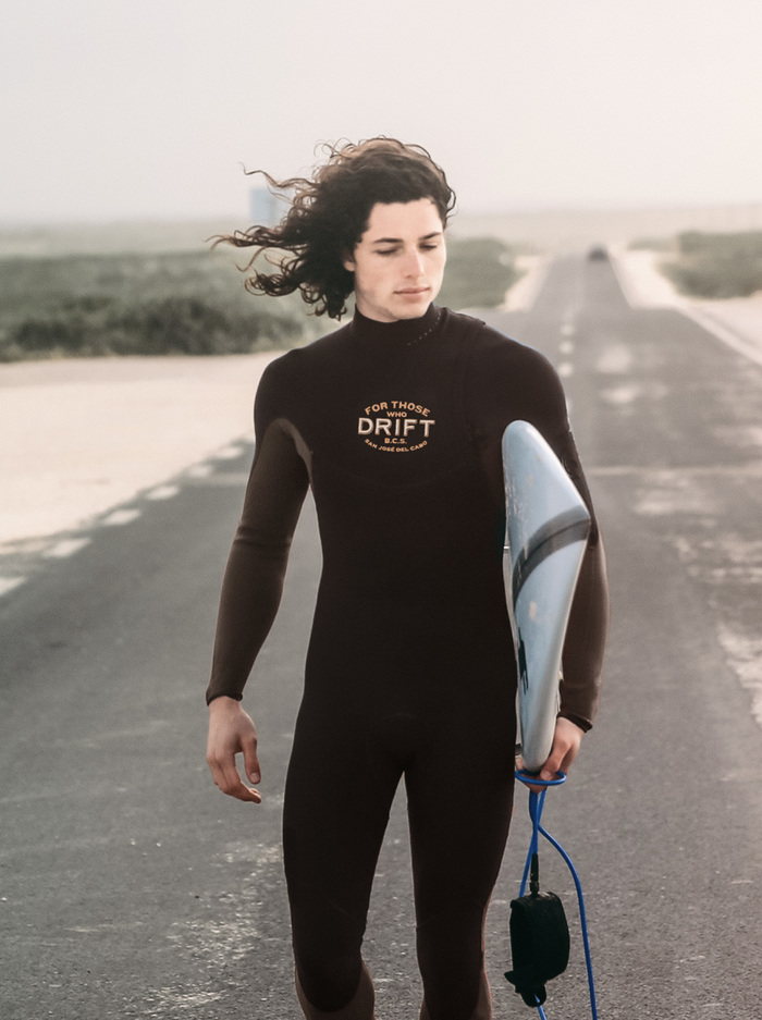 Surfer walking with surfboard in a Drift branded wetsuit