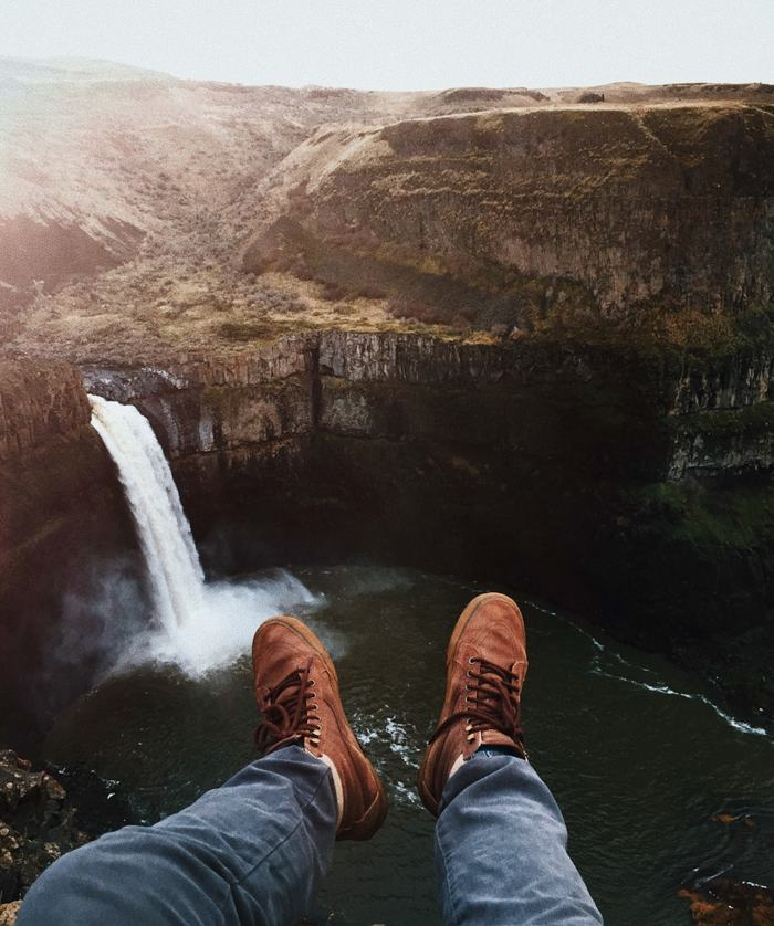 View of a large waterfall with photographer's legs sticking out into the void