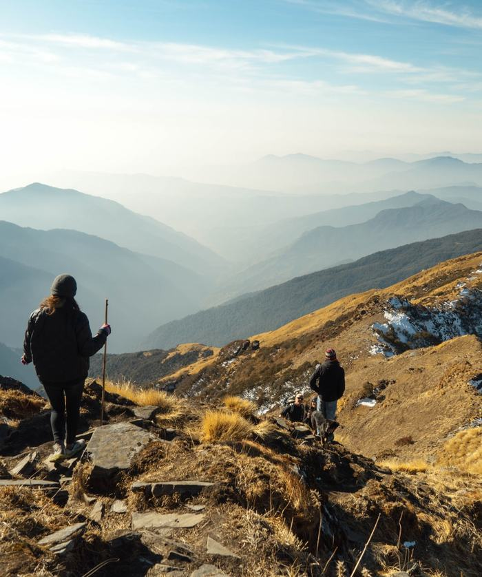 Hikers on a rocky mountain top with an expansive mountain and valley view in the distance