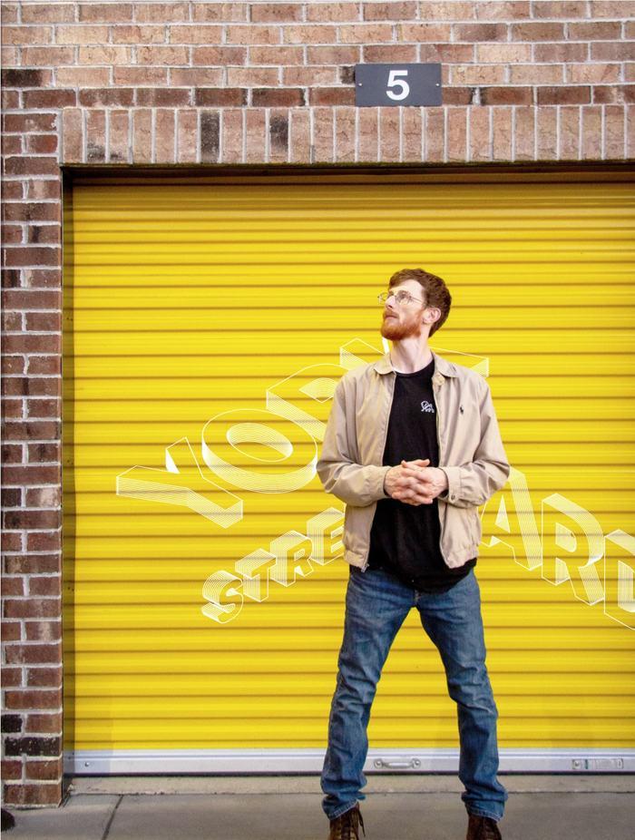Bearded man standing in front of York Street Yards branded garage door
