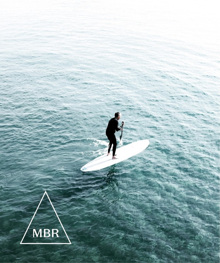 Overhead shot of paddle boarder in the middle of the ocean with the shortform MBR logo in the corner