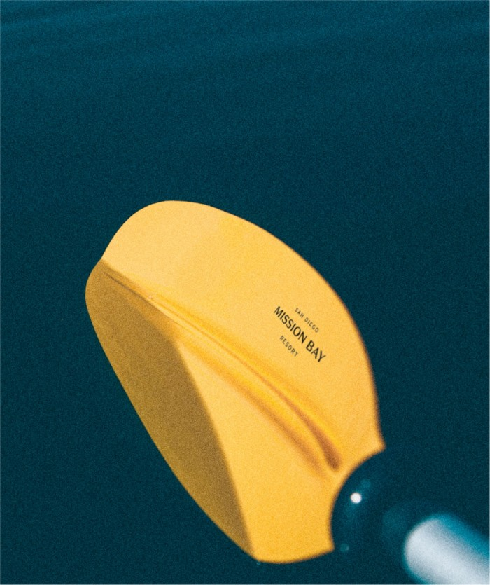 Closeup of yellow kayak paddle in the water with MBR logo