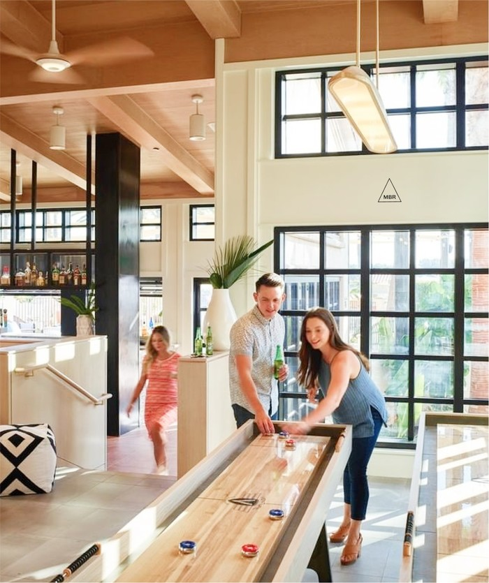 Interior of MBR with couple playing shuffleboard in light, bright common area