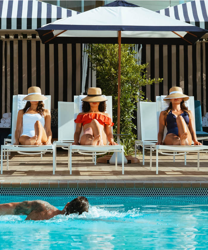 Women laying by the pool at Beach Village