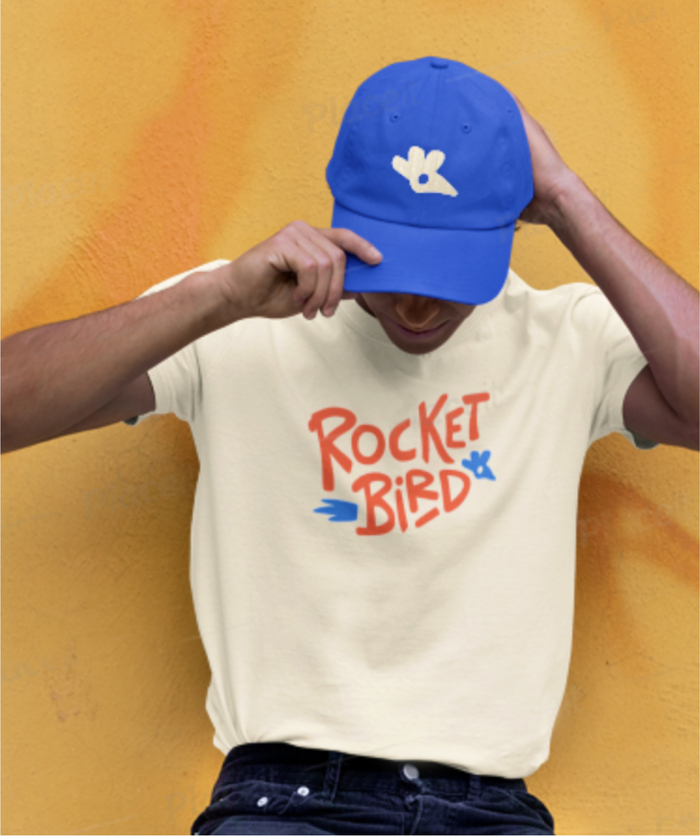 Person posing against yellow wall wearing white rocketbird sandwich and blue rocketbird hat